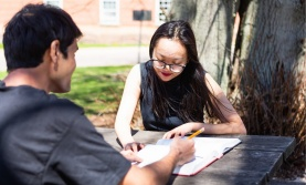 Two students studying outside at a picnic table