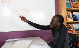 Student pointing at an equation written on a whiteboard
