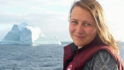Photo of Caroline Merner with ocean and icebergs in background.