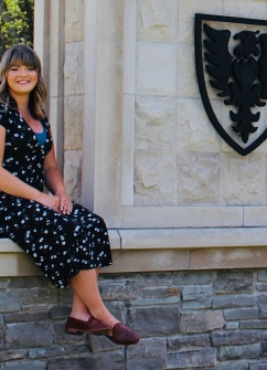 Photo of Jessica MacKeen sitting on a wall at Dalhousie