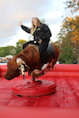 Student riding a bucking-bronco machine