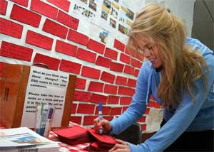 Student writing on brick