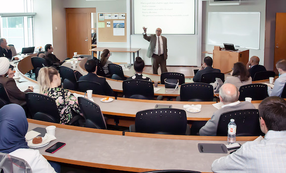 A speaker from a previous workshop stands at the front of the room with their arm raised, addressing the audience.
