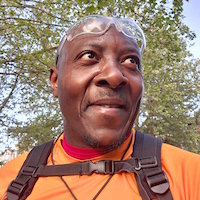 Stanley Asah in an orange shirt, backpack straps buckled across his chest. He is wearing glasses on his forehead. The leaves of a tree can be seen behind him.