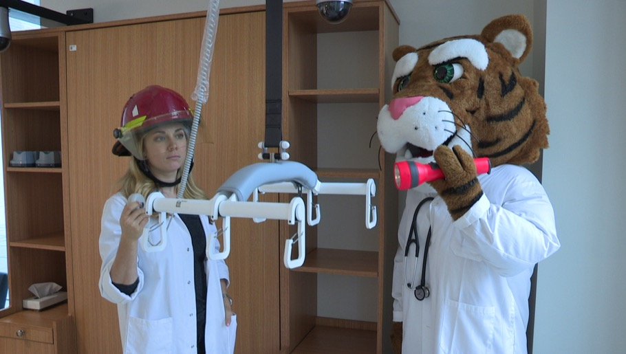 Professor wearing firefighter helmet with face shield and tiger mascot holding flashlight operating patient transfer lift