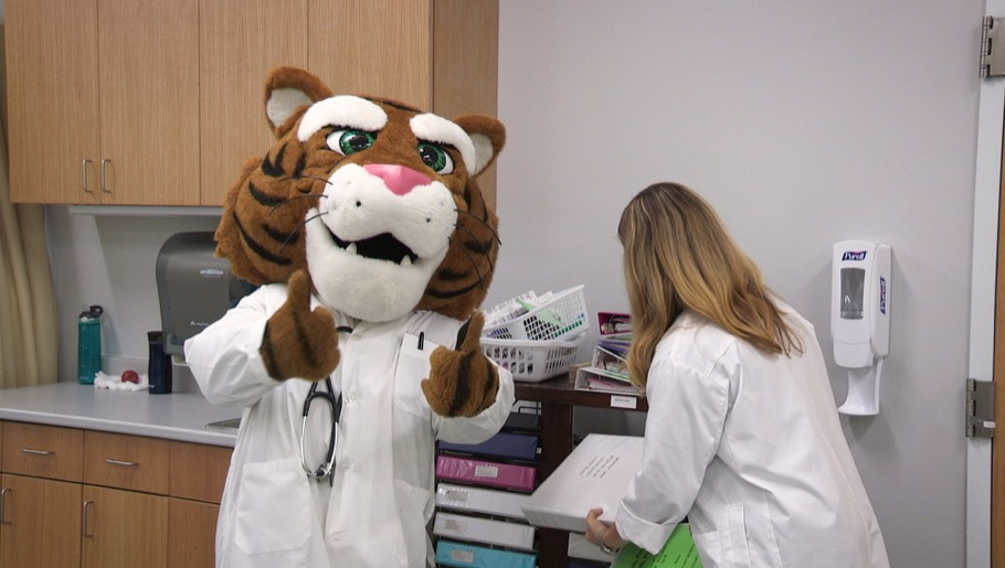 Tiger mascot giving thumbs up sign while professor puts away equipment