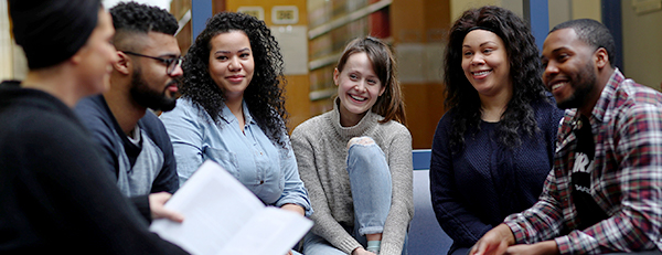 A group of students sit in a semi-circle, smiling at each other. One holds an open book. Library shelves can be seen in the background.