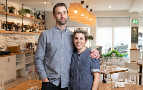 Doug Townsend and Renée Lavallée stand in their kitchen with arms around each other, smiling.