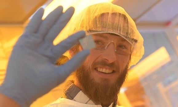 A man holding a solar cell close to the camera while wearing protective equipment in a lab