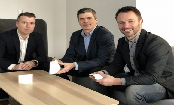 The three founders of Adaptiiv Medical Technologies sitting at a table, holding 3D printed materials