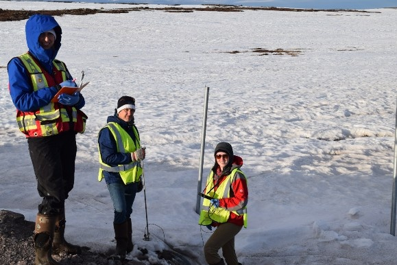 A photo of three researchers standing in the snow in Baker Lake, Nunavut.