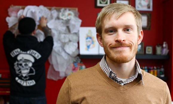 Researcher/inventor Alec Falkenham is photographed inside of a tattoo studio.