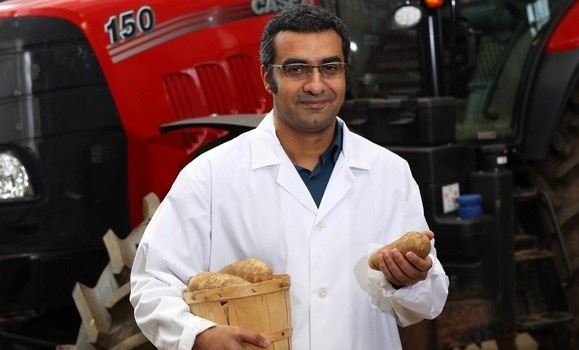Dr. Ahmad Al-Mallahi is photographed wearing a lab coat and protective eyewear standing in front of a tractor holding a basket of potatoes.