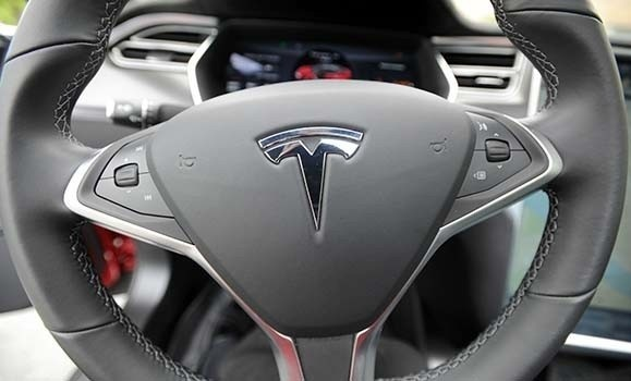 A photograph of a steering wheel with the Tesla logo in the middle