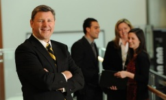 A man faces the camera,smiling. In the background, 3 others' are having a discussion.