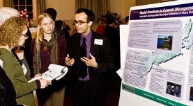Two graduate students present a poster to someone with a clipboard