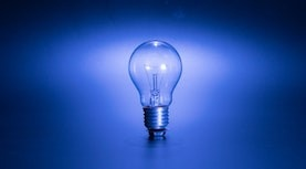 An illuminated light bulb. The photo is tinted blue